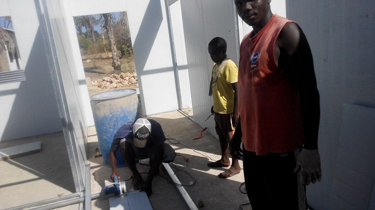 Prefab House Project In Kenya, A Native Worker Is Cutting A Wall Panel.