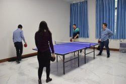 Foreign trader playing table tennis with customers