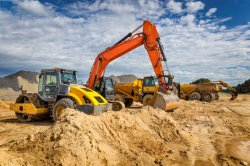 excavator and road roller working site