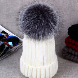 冬の上の帽子によって編まれる帽子の毛皮の球