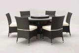 セットされる円形の灰色の藤のダイニングテーブルおよび6脚の食事の椅子