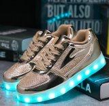 O diodo emissor de luz luminoso do esporte das sapatas do miúdo das crianças ilumina acima sapatas do instrutor da escola