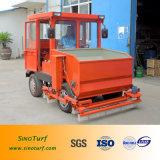 La máquina del césped, máquina sintetizada del césped, césped instala la máquina (el infill diesel y aplica la máquina con brocha)
