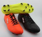 運動履物の人のフットボールは屋外のサッカーの靴を起動する