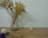 La soia esamina in controluce la tazza di vetro, candela profumata, che non dà fumo, non tossica