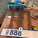 Manual de mão pressionando a máquina para a placa com o número de licença do carro