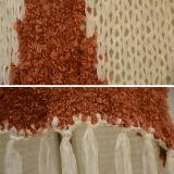 女性は長いフリンジのヘムによって編まれるカーディガンを作る