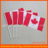 Fördernde Kanada-Hand, die Markierungsfahnen mit Polen rüttelt