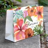 Saco de papel luxuoso do presente da compra com a cópia do logotipo para vestuários