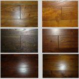 Raspa la mano de color oscuro con pisos de madera de teca de Mongolia