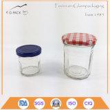 Un insieme di 2 vasi di vetro del miele con la protezione stampata del metallo
