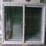 Один из зеленого стекла белой рамкой скользящего окна из ПВХ