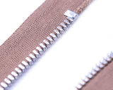Chiusura lampo del metallo con i denti d'argento lucidi di colore ed il tenditore operato/superiore