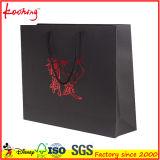 Sac de papier de sortie d'usine de cadeau noir de luxe fait sur commande d'OEM avec le traitement en soie de bande pour la femme