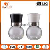 La mano de la botella de cristal funciona el molino de la sal y de pimienta