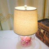 장식적인 배열은 선물로 유리제 책상용 램프에 있는 꽃을 보존했다