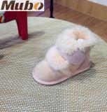 かわいいピンクの毛皮の羊皮の幼児は幼児ブートに蹄鉄を打つ