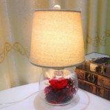 Arreglos decorativos de flores rosas conservadas en la cúpula de cristal lámpara de escritorio