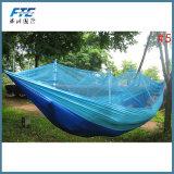 屋外蚊帳が付いているキャンプのハンモックを運ぶ