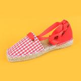 La tela di canapa classica del plaid merletta in su i pattini rossi e bianchi delle scarpe di tela
