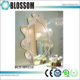 Mano che intaglia lo specchio rotondo della parete decorativa a forma di del fiore