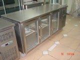 Acero inoxidable bajo el refrigerador contrario con la puerta de cristal