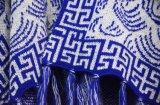 女性は青い民俗フリンジのカーディガンのセーターを作る