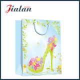 Sandalias de tacón alto de la señora de la manera mano que hace compras el bolso de papel del regalo