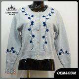女性の方法刺繍の青いボタンによって編まれるカーディガン