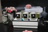 As velas perfumadas na jarra de vidro branco com grande caixa de oferta
