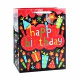 A roupa do ornamento da vela do aniversário calç os sacos de papel do presente atual
