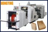 Una capa de pulgar cortando el tubo de papel que hace la máquina La máquina de bolsa de papel