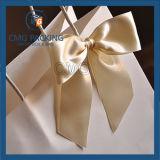 실크 리본 나비 넥타이를 가진 사랑스러운 종이 봉지는 붙였다