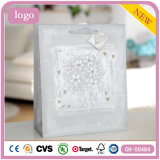 Flores brancas que vestem os sacos de papel do presente dos cosméticos das sapatas das lembranças