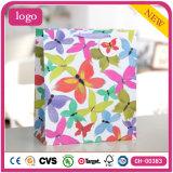 A roupa de forma colorida do teste padrão de borboleta calç os sacos de papel do presente