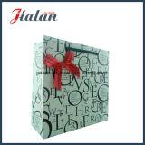 Cor branca com o saco de papel do presente da compra da mão das letras pretas