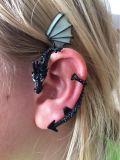 El oído del dragón en los pendientes plateados oscuros del dragón