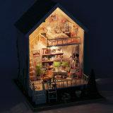 Casa de muñeca de madera hecha a mano con los juguetes educativos para los cabritos