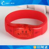 L'usager d'événement de concert allument le bracelet vers le haut de clignotement de DEL