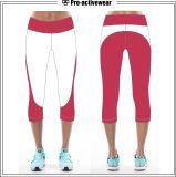 Stirata delle donne che esegue i pantaloni atletici di yoga di Capri di forma fisica di Crossfit