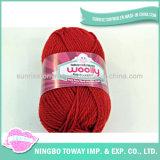 Lavoro a maglia dei guanti che tessono il filato di lana puro