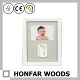 新しい赤ん坊のギフトの安全な粘土が付いている木製の赤ん坊映像の写真フレーム