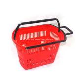 O rolamento e a mão do supermercado carreg a cesta de compra plástica com rodas
