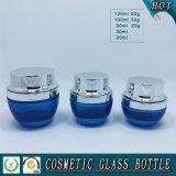 голубые покрашенные бутылки и опарникы косметики упаковывая стеклянные
