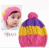 子供か赤ん坊はかぎ針編みの帽子の帽子か帽子を編んだ