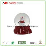 يد يدهن راتينج حرفة هبات ماء كرة أرضيّة مع رجل ثلج لأنّ ترويجيّ هبات وعيد ميلاد المسيح زخرفة