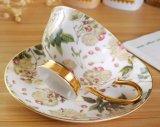 Taza de cerámica del oro con la taza de la porcelana del platillo con el platillo
