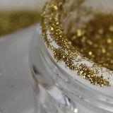 El polvo de oro del brillo en el polaco de clavo bonito