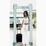 Caminata de la seguridad de la seguridad del aeropuerto a través del detector de metales que detecta la puerta