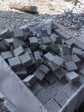 薄い灰色の花こう岩の立方体は花こう岩の縁石を炎にあてた